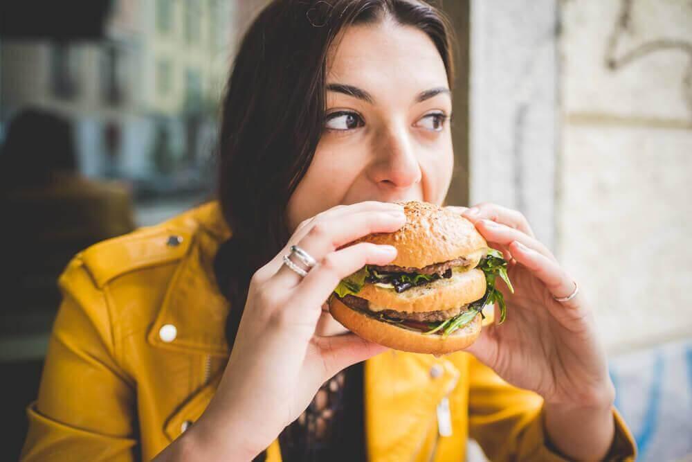 Donna che mangia hamburger