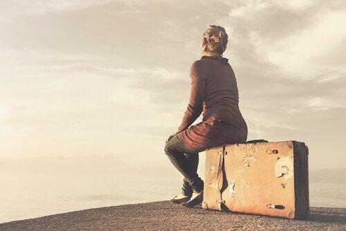 Donna seduta su una valigia
