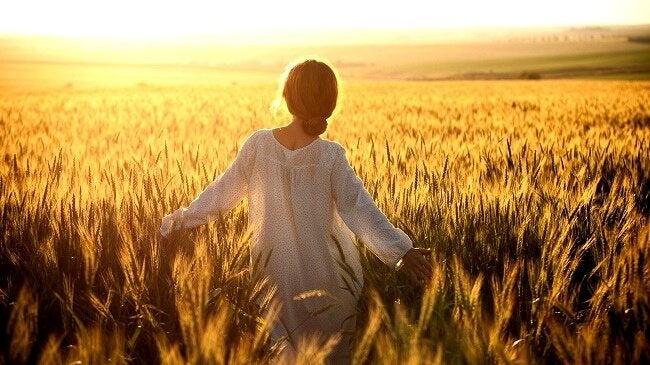 Donna vestita di bianco che cammina in campo di grano