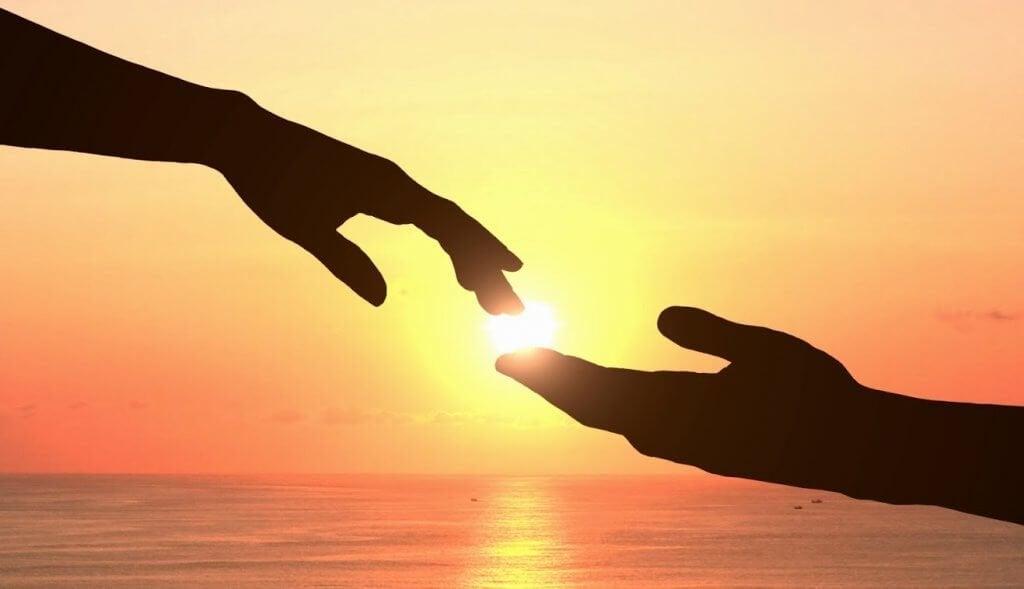 Mani che si toccano al tramonto