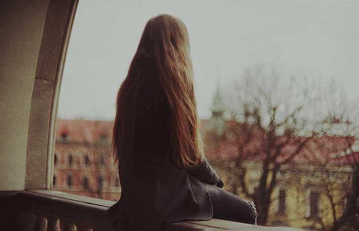 Ragazza seduta sul davanzale della finestra