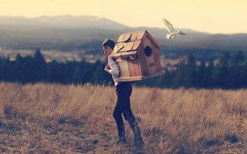 Ragazzo che porta una casa sulle spalle