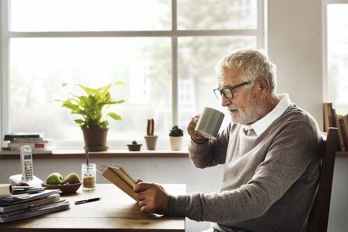 Uomo anziano con tazza e libro