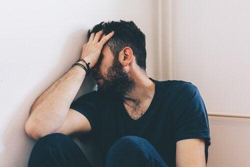 Uomo disperato con la testa appoggiata alla parete