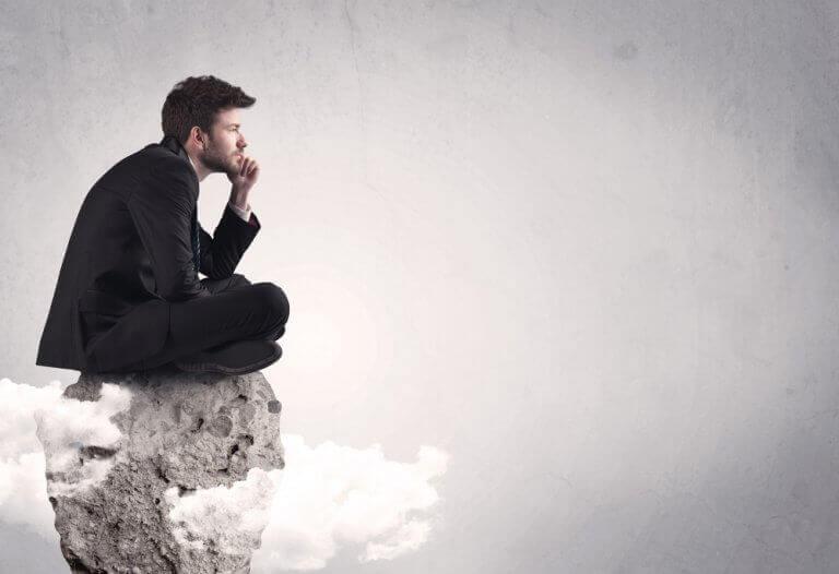 Uomo pensa seduto su una roccia
