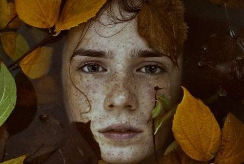 Volto nell'acqua circondato da foglie