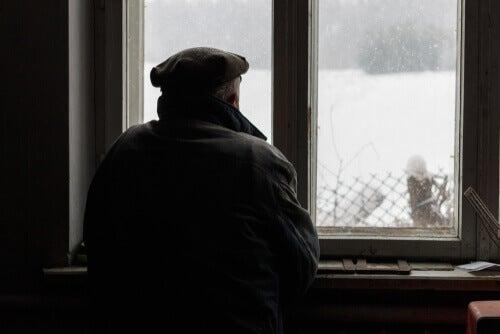 Anziano che guarda la neve dalla finestra