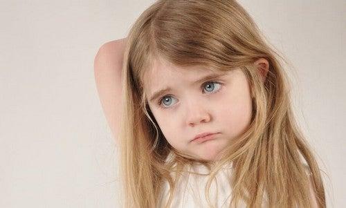 Bambina preoccupata a causa di genitori emotivamente assenti