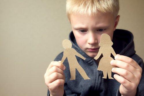 Bambino che guarda sagome genitori di carta