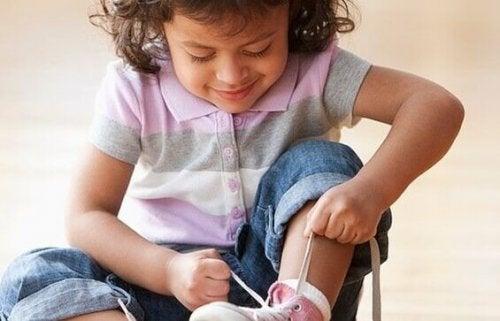 Bambina si allaccia le scarpe