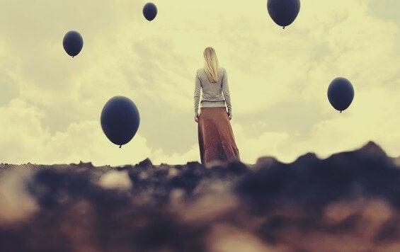 Donna che guarda cielo con palloncini neri