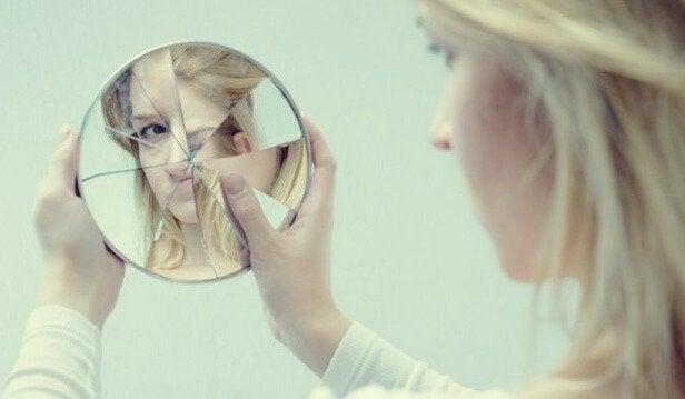 Donna che si guarda in specchio rotto