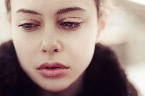 Donna con volto triste che guarda in basso