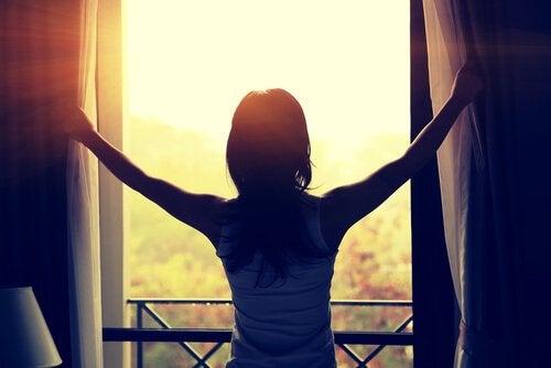 Donna di spalle guarda il sole alla finestra