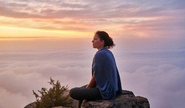 Donna tra le nuvole seduta su una roccia