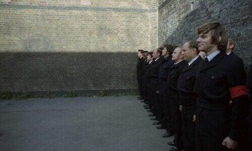Fila di uomini con spalle al muro
