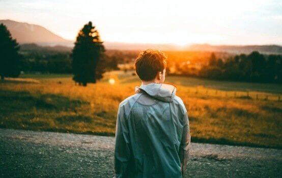 Ragazzo all'aperto di spalle al tramonto