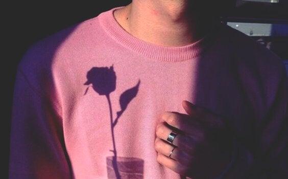 Ragazzo con la mano sul cuore e l'ombra di una rosa sulla maglia