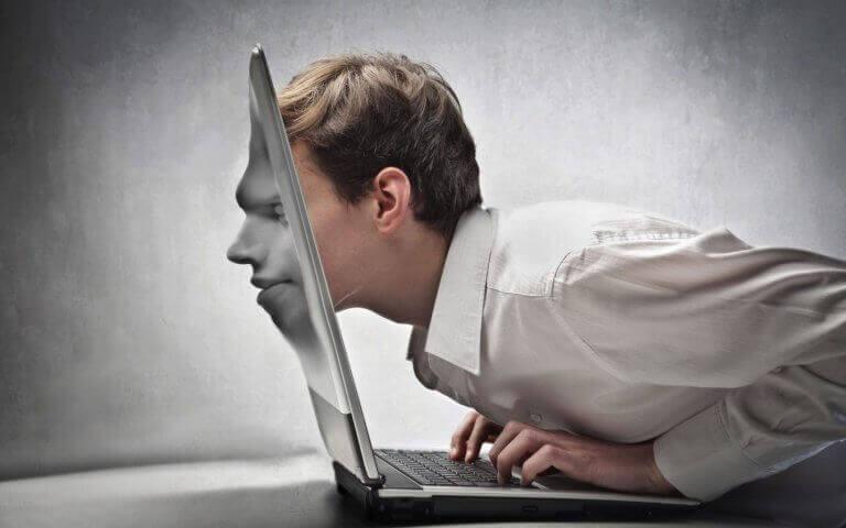 Uomo con il viso assorbito dallo schermo del portatile