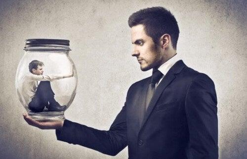 Uomo dentro una palla di vetro sostenuta da un altro uomo