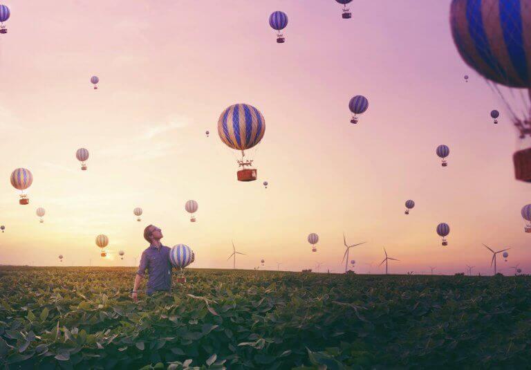 Uomo in un campo osserva delle mongolfiere in cielo