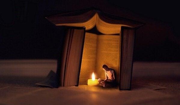 Uomo seduto sotto libri giganti
