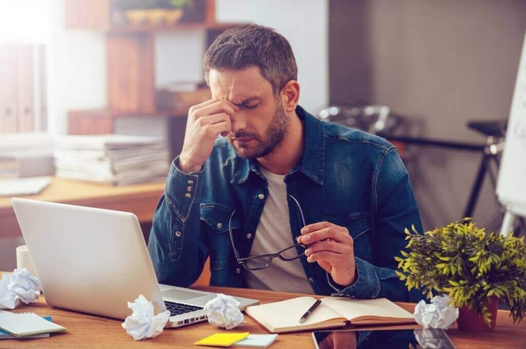 Uomo stressato di fronte al computer a occhi chiusi