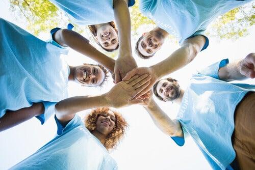 Volontari con maglietta celeste in cerchio tenendosi per mano