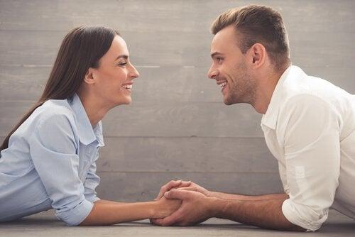 Coppia che si guarda e sorride tenendosi per mano