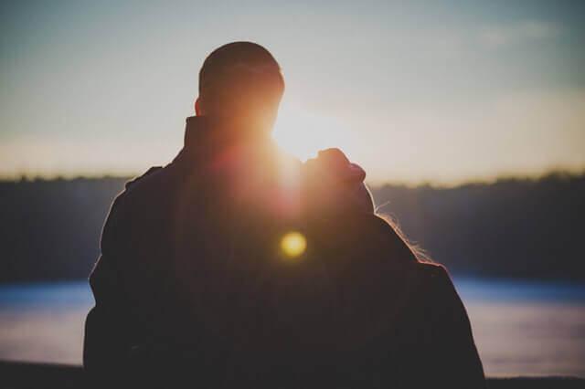Coppia di spalle con donna che appoggia testa su uomo