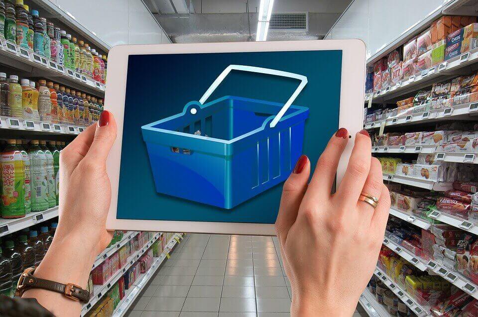 Donna con tablet al supermercato