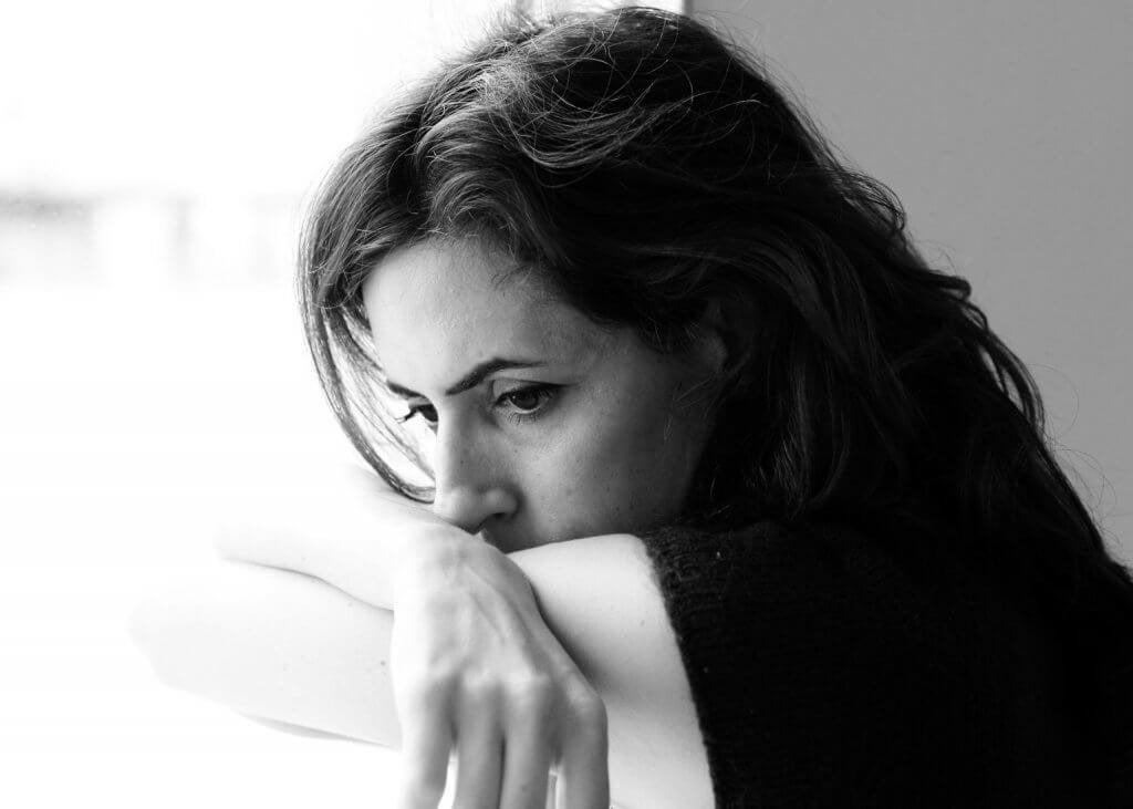 Donna triste appoggiata sulle mani infelici sul lavoro