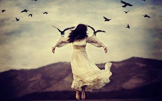 Donna vestita di bianco sorretta da uccelli