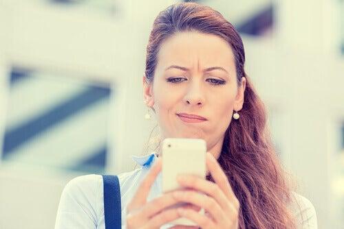 Donna che fa smorfia guardando il cellulare