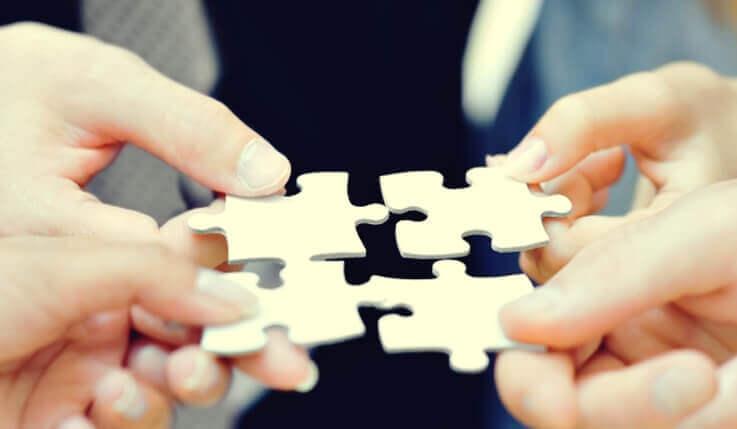 Mani che uniscono pezzi di puzzle