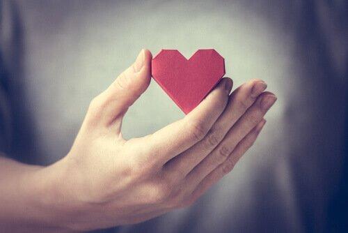 Cuore di carta tra le dita a indicare le emozioni represse
