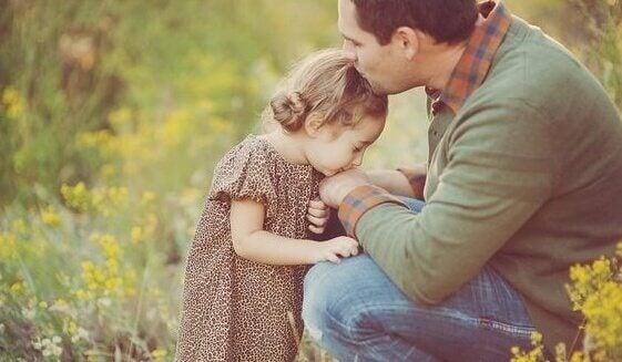 Padre che dà bacio su fronte a sua figlia