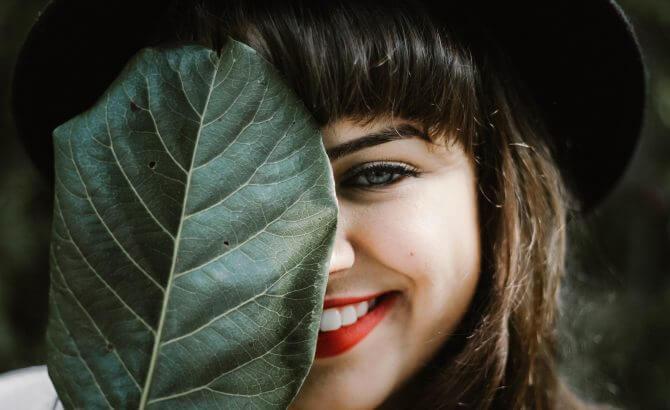 Ragazza che sorride dietro a foglia
