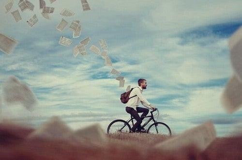 Ragazzo in bicicletta con fogli che escono dallo zaino