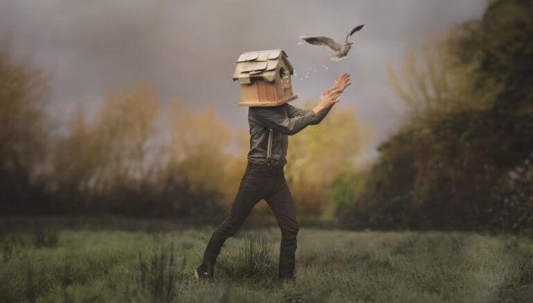 Uomo con la testa a forma di casetta per ucellini