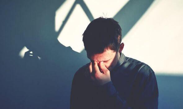 Uomo triste con mano sul volto e occhi chiusi