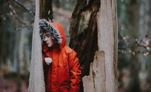 Bambino in foresta con giacchetto rosso