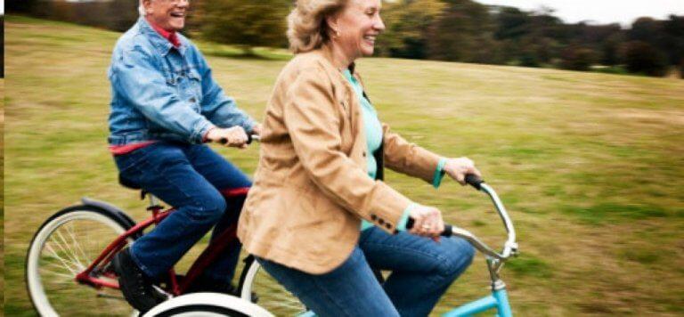 Coppia anziana felice in bicicletta