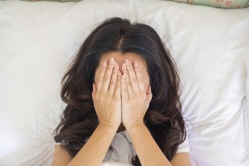 Donna a letto con le mani sul viso