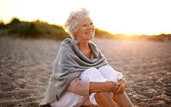 Donna anziana da sola e sorridente seduta su spiaggia