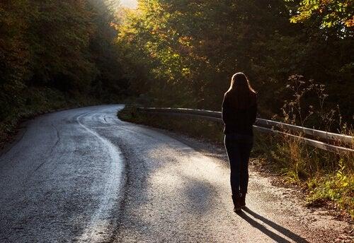 Donna cammina su strada asfaltata di montagna