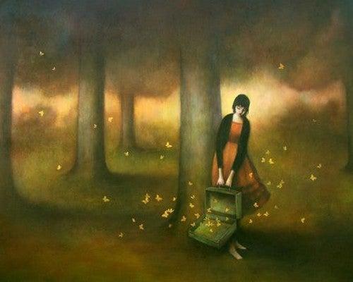 Donna con una valigia nel bosco