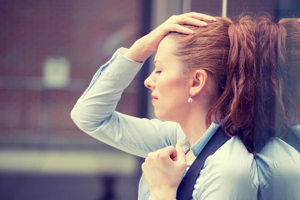 Donna frustrata con occhi chiusi e mano su testa