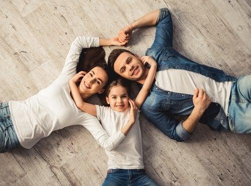 Famiglia abbracciata e distesa sul pavimento