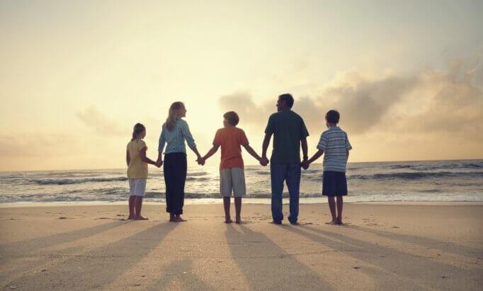 Famiglia si tiene per mano sulla spiaggia